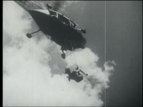 b/w low angle woman hanging from two rings from helicopter in air / nyc - stunt person stock videos & royalty-free footage