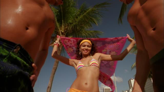 Low angle woman in bikini dancing outdoors w/two barechested men