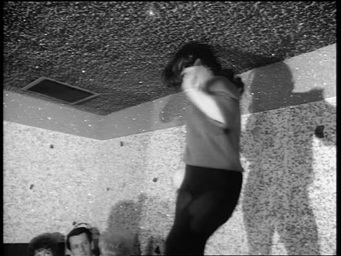 b/w 1965 low angle woman in black tights dancing on table in nightclub / newsreel - klassischer rock and roll stock-videos und b-roll-filmmaterial