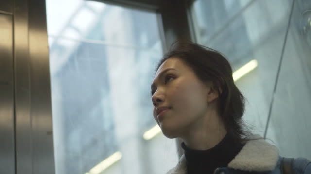 Low angle, woman in elevator