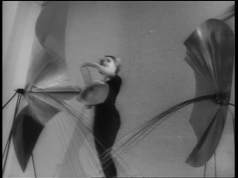 vidéos et rushes de b/w 1964 low angle woman in leotard dancing thru metal sculpture / paris / newsreel - représentation artistique