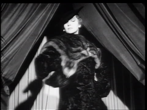 b/w 1934 low angle woman modeling fur coat turning in front of curtain / new york city - 1934 stock videos & royalty-free footage