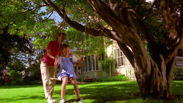 low angle woman pushing young girl on swing hanging from tree in yard / house in background