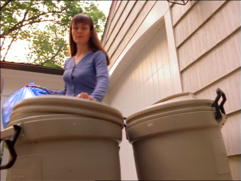vídeos de stock e filmes b-roll de low angle woman putting full blue garbage bag into outdoor garbage can - lixo