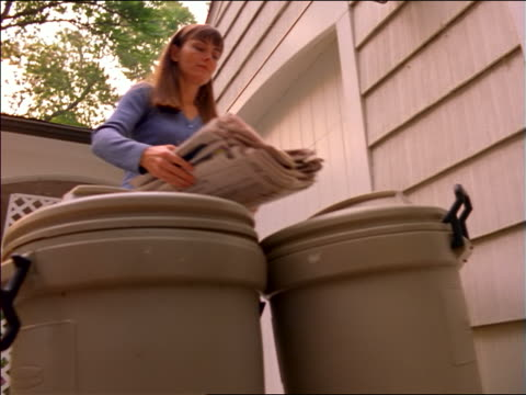 low angle woman putting stack of newspapers on top of outdoor garbage cans