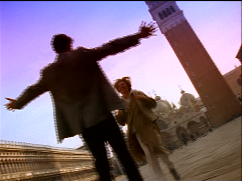 stockvideo's en b-roll-footage met canted low angle woman running to + hugging man in piazza san marco / venice, italy - romance