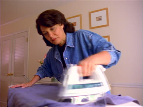 stockvideo's en b-roll-footage met low angle woman steaming + ironing on ironing board - strijkijzer