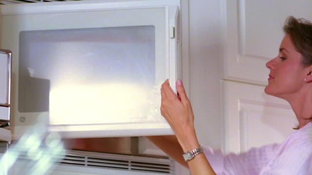 vidéos et rushes de low angle pan woman taking container of food out of microwave - four à micro ondes
