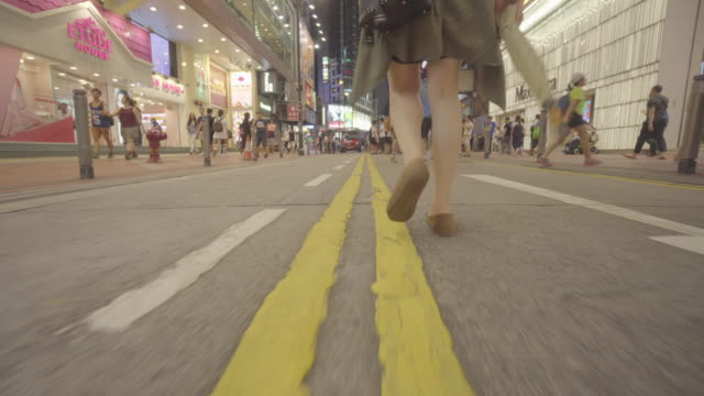 low angle, woman walks down street in hong kong - tracking shot stock videos & royalty-free footage