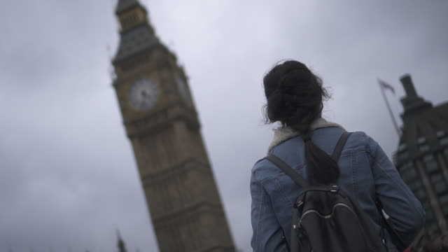 Low angle, woman walks past Big Ben in London