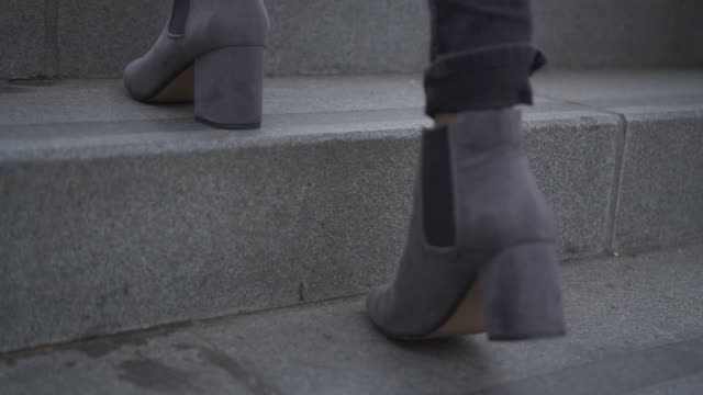low angle, woman walks up staircase in london - staircase stock-videos und b-roll-filmmaterial