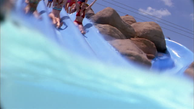 Low angle women holding hands and sliding down water slide into pool