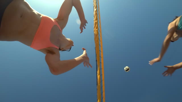 low angle pov of women players playing beach volleyball from below. - slow motion - sun visor stock videos & royalty-free footage