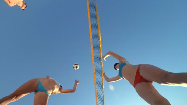 low angle pov of women players playing beach volleyball from below. - slow motion - bikini bottom stock videos & royalty-free footage