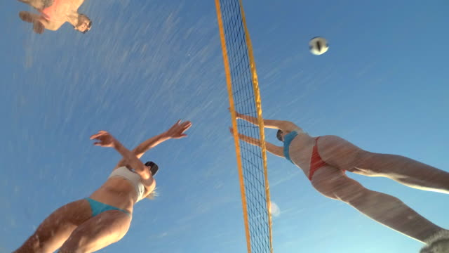 low angle pov of women players playing beach volleyball from below. - slow motion - competition stock videos & royalty-free footage