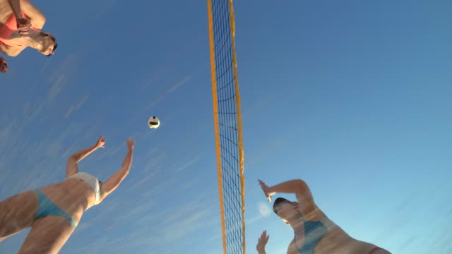 vidéos et rushes de low angle pov of women players playing beach volleyball from below. - slow motion - droit