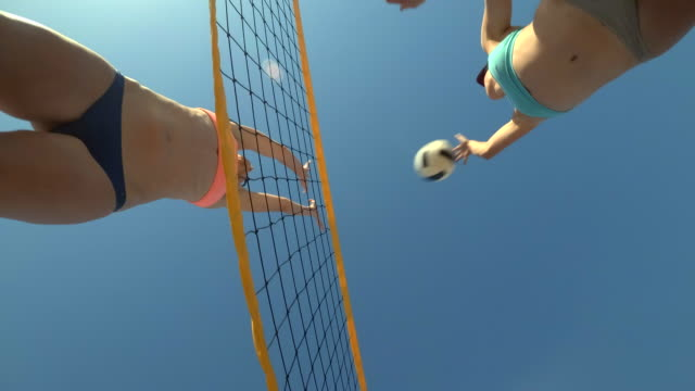 low angle pov of women players playing beach volleyball from below. - slow motion - low angle view stock videos & royalty-free footage