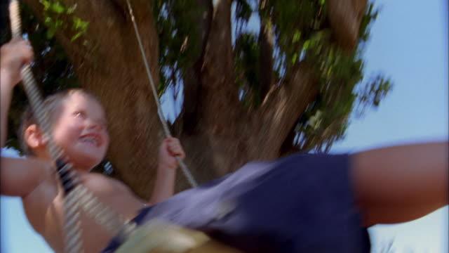vídeos y material grabado en eventos de stock de low angle young boy swinging on tree swing and smiling - columpiarse