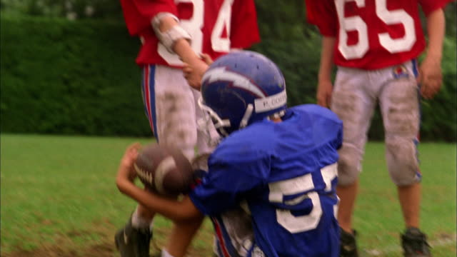 Low angle young football player helping fallen boy get up from field