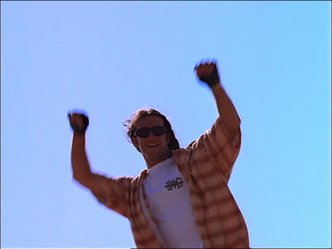 low angle young generation x man in sunglasses turning to camera + raising arms in victory + cheering - x世代点の映像素材/bロール