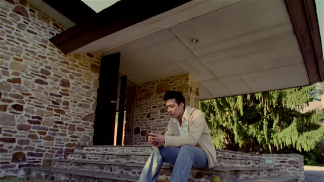 low angle young man sitting on steps of stone house using cell phone - stone house stock videos & royalty-free footage