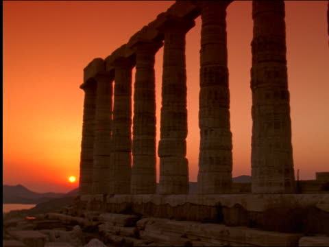 low angle zoom in columns of temple of poseidon at sunset / aegean sea in background / cape sounion, greece - sounion stock videos and b-roll footage