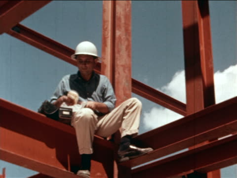 1964 low angle zoom in construction worker in hard hat sitting on metal beam eating sandwich / industrial