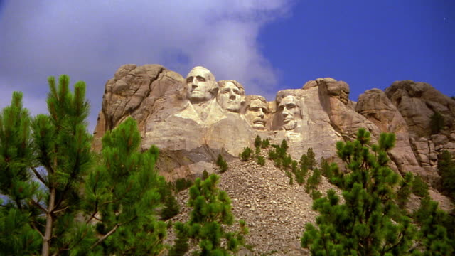 low angle zoom in from wide shot Mount Rushmore National Memorial / pine trees in foreground / South Dakota