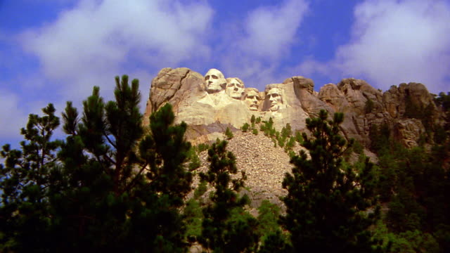 low angle zoom in from wide shot mount rushmore national memorial / pine trees in foreground / south dakota - mt rushmore national monument stock videos and b-roll footage