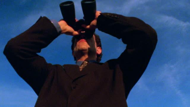 low angle zoom in man in suit looking through binoculars - binoculars stock videos & royalty-free footage
