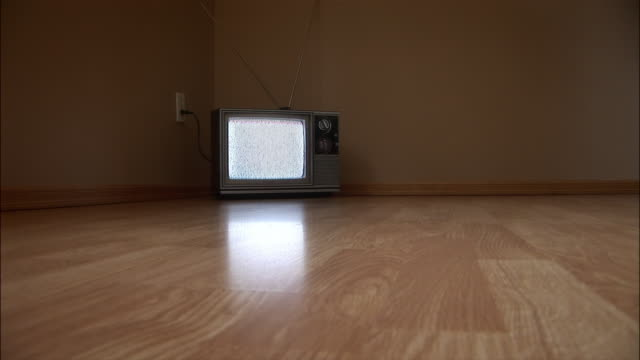 low angle zoom in television set sitting in corner of room on the floor / plugged into outlet and showing static - television static stock videos & royalty-free footage
