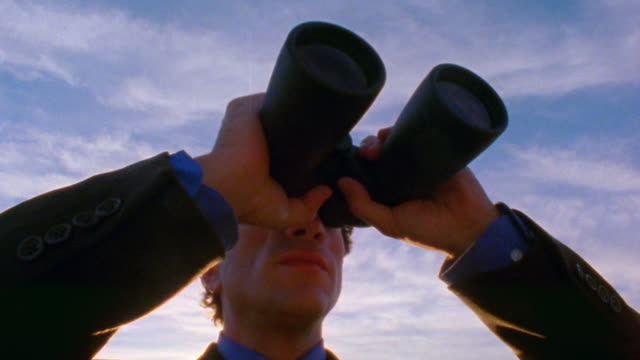 low angle zoom in to extreme close up man in suit looking through binoculars outdoors