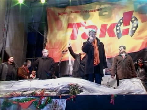 2004 low angle zoom in Yushchenko gesturing to audience from stage at Orange Revolution campaign rally / Ukraine