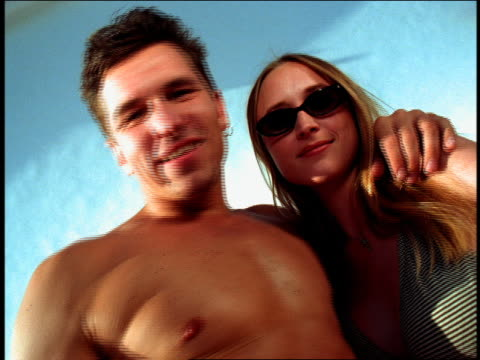 vídeos de stock e filmes b-roll de low angle zoom in zoom out young couple posing against white background / man is shirtless / california - super exposto