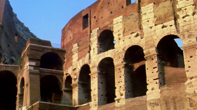 low angle ms zoom out pan arches of the colosseum in rome / italy - arco architettura video stock e b–roll