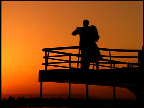 orange silhouette low angle zoom out couple dancing on deck of cruise ship at sunset / nile river, egypt - 中年カップル点の映像素材/bロール