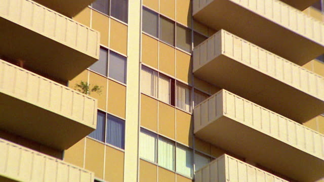 vidéos et rushes de low angle zoom out from close up window to medium shot apartment building with yellow trim and balconies - zoom out
