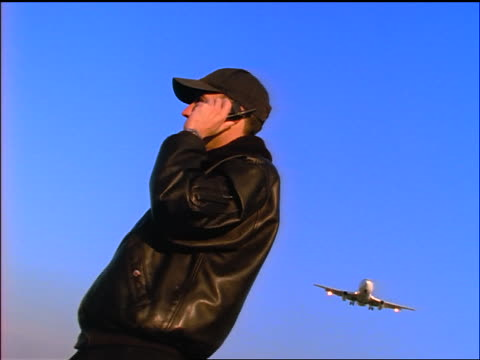 vidéos et rushes de low angle zoom out man in black leather jacket talking on cellular phone as airliner flies overhead - casquette de baseball