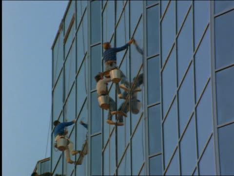 vídeos de stock e filmes b-roll de low angle zoom out of window washers on building - cinematografia