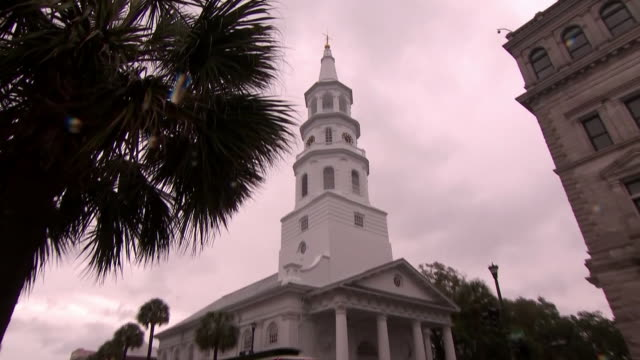 vidéos et rushes de ws low angle zoom out on palm tree next to white church with bell tower church with pillars stands on the corner of street in charleston south... - clocher élément architectural