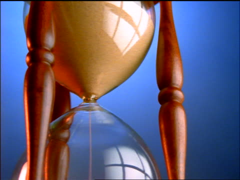 low angle zoom out sand falling in spinning hourglass - 1998 stock videos & royalty-free footage