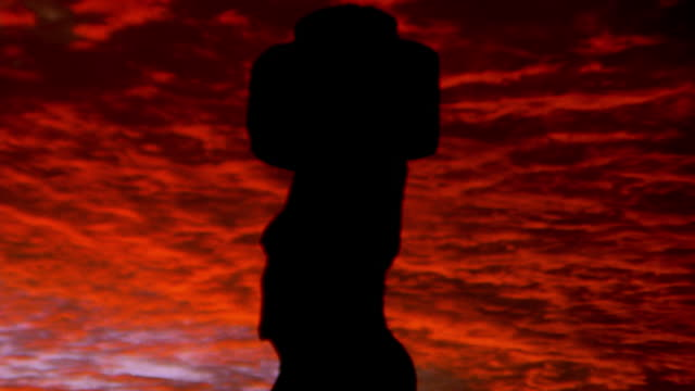 low angle zoom out to wide shot of stone moai statue on easter island at dusk / south pacific - maui stock videos & royalty-free footage