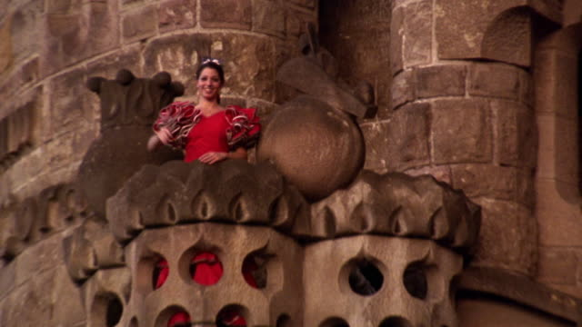 low angle zoom out zoom in woman in red flamenco dress waving + blowing kisses from balcony of Sagrada Familia