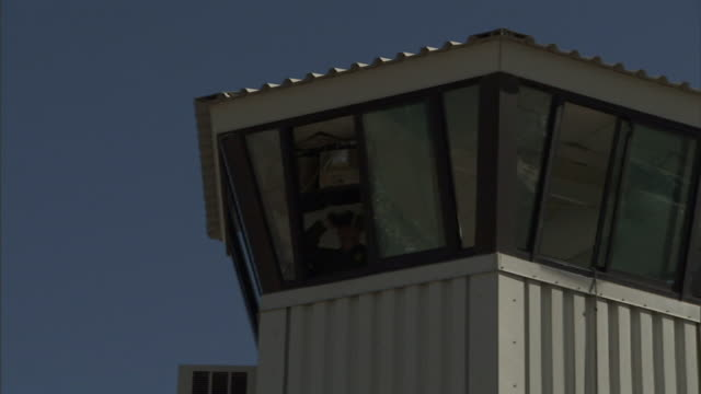 Low Angle zoom-out - A prison guard in a watchtower uses binoculars. / California, USA
