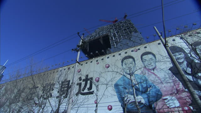 low angle_hand-held tracking-left - bare trees border a graffiti-covered wall.   - 囲み塀点の映像素材/bロール