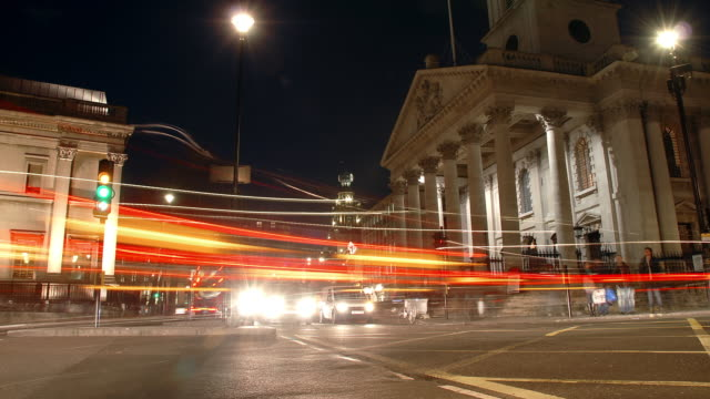 Low angled view of city traffic rapidly passing the frame with the portico of St Martin-in-the-Fields on the east side of Trafalgar Square in the background