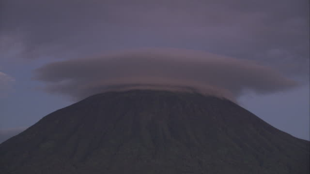 A low bank of cloud shrouds volcano summit. Available in HD.