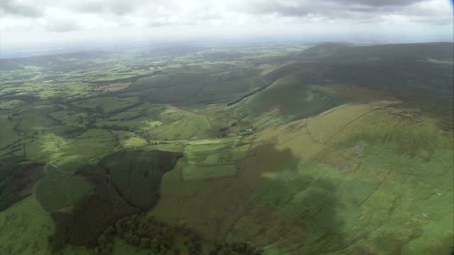 A low bank of clouds casts shadows across the lush British countryside. Available in HD.