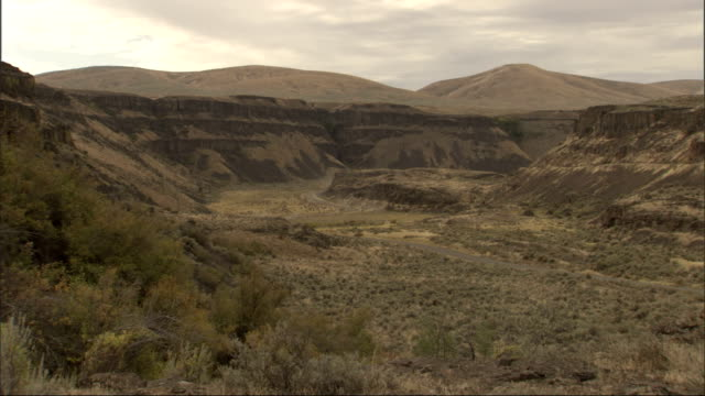 low barren mountains surround a distant highway stretching through desert scrubland. available in hd. - shrubland stock videos & royalty-free footage