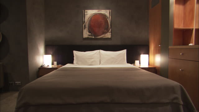 Low bedside lights illuminate a hotel room.